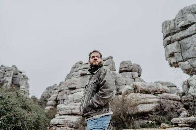 脇を見て岩の崖の近くに立っているジャケットを着た若い男性