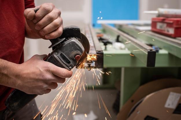 산업 도구로 뭔가 만드는 빨간 스웨터와 젊은 남성