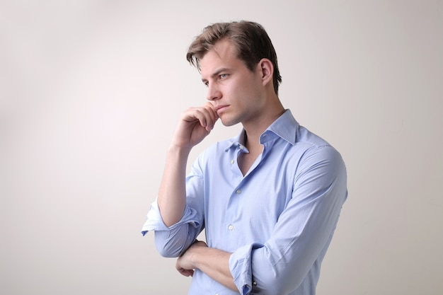 Young male with a blue shirt having deep thoughts standing against a white wall