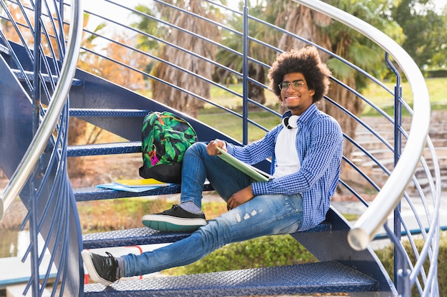 Young male with book and bags relaxing on the blue staircase in the park