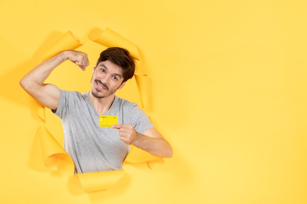 Young male with credit card flexing on yellow paper background money bank sale shopping