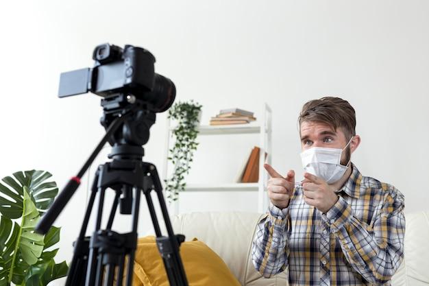 Молодой мужчина с маской для лица, записывая видео дома