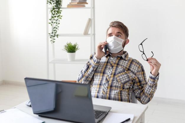 電話で話しているフェイスマスクを持つ若い男性