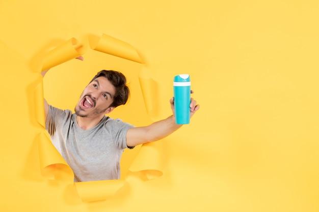 Молодой мужчина с зеленой бутылкой на желтом фоне спорт спортсмен тренировки тренажерный зал упражнения подходят