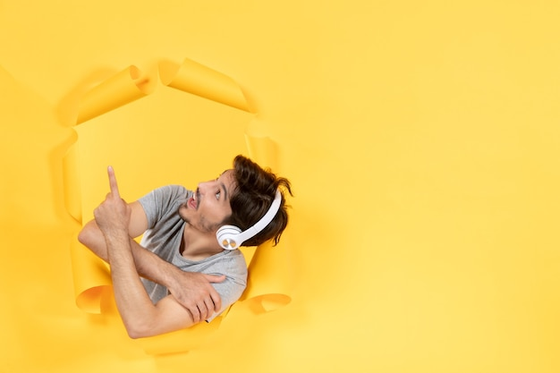 노란색 종이 배경 초음파 음악 오디오 위에서 헤드폰을 끼고 있는 젊은 남성