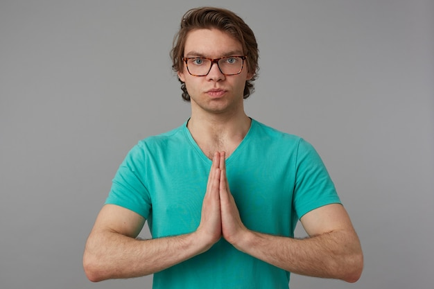 Young male with serious concentrated facial expression, looks into camera while keeps his palms together in praying position. isolated over gray background