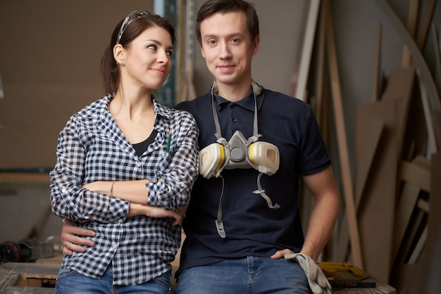 Young male and woman joiners sitting in workshop on background of boards