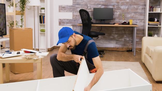 새 집에 있는 가구의 젊은 남성 작업자 조립 세부 정보, 가구 조립 도구.