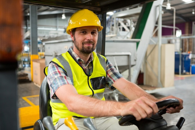 Giovane lavoratore maschio guida carrello elevatore in magazzino