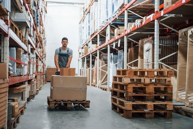 Молодой рабочий в военной форме толкает тележку с поддонами на складе.