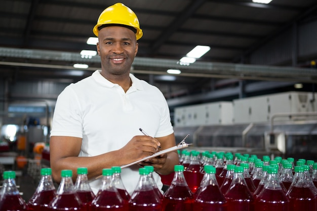Young male worker noting in juice factory