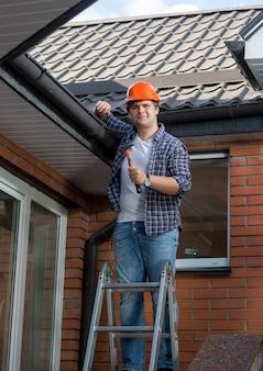 Молодой работник мужского пола, стоящий на стремянке перед домом