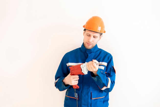 A young male worker in uniform holding the electrical tool drill