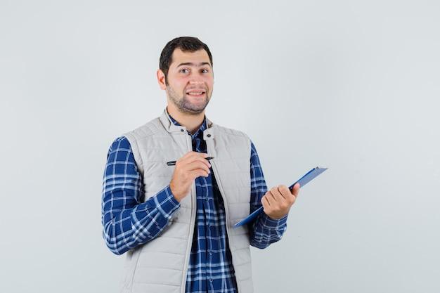 Giovane maschio che scrive qualcosa in camicia, giacca e sembra soddisfatto. vista frontale.