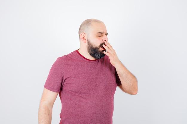 Молодой мужчина зевает в розовой футболке и выглядит сонным. передний план.