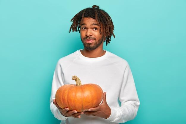 Giovane maschio giovane con i dreadlocks, poca barba, indossa un maglione bianco casual, tiene la zucca arancione, si prepara per la celebrazione delle vacanze