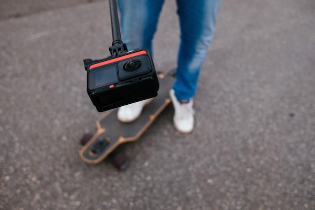 Молодой мужчина-ютубер снимает себя для видео с лонгбордом