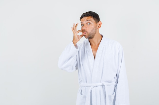 Young male zipping his mouth shut in white bathrobe and looking careful. front view.