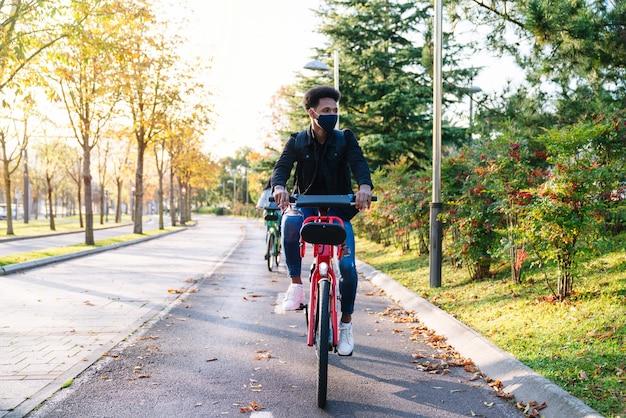 Молодой человек, марокканский студент, катающийся на общем электрическом велосипеде в красивом парке с множеством деревьев на закате, в маске для лица во время пандемии коронавируса 2020 года