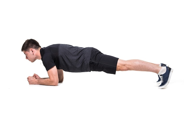 Young man on abdominals workout basic plank posture on white