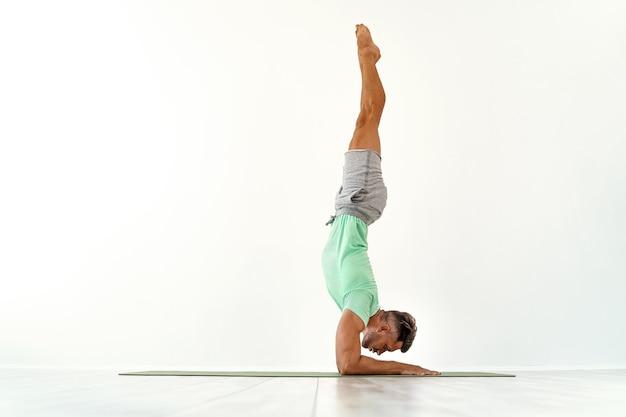 Гимнастический молодой человек делает стойку на руках в студии, изолированной на белом спортивном спортсмене