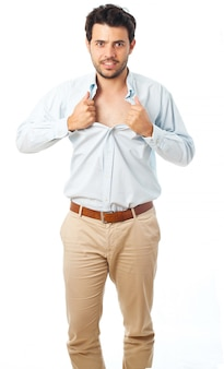 Young man acting like a super hero and tearing his shirt off on a white background