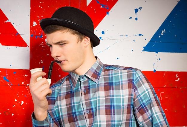 Молодой человек, изображающий идеального типичного английского джентльмена в котелке и трубке, позирует перед национальным флагом юнион джек, нарисованным на стене