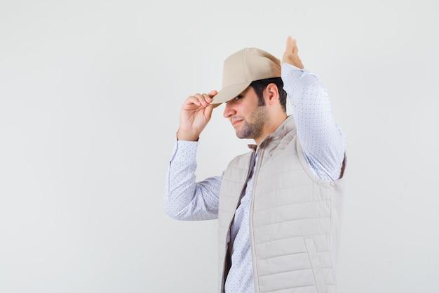 シャツ、ノースリーブのジャケットを脇に見ながら、気配りをしながらキャップを調整する若い男。