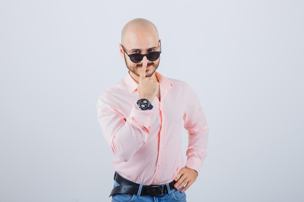 Young man adjusting glasses in pink shirt,jeans and looking cool. front view.