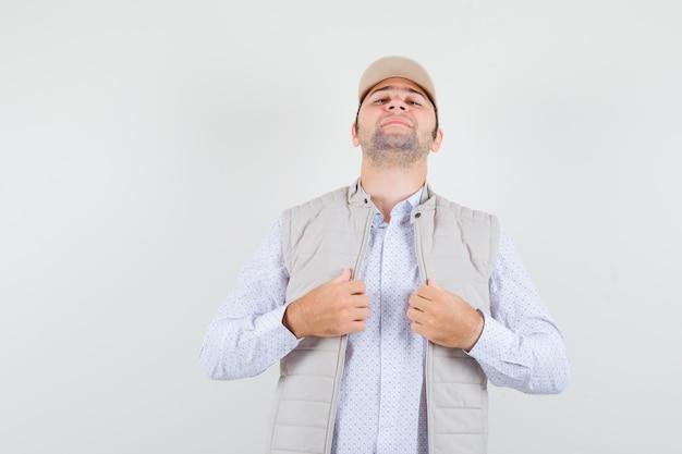 若い男はシャツ、ノースリーブのジャケット、キャップで彼の襟を調整し、自信を持って見えます。正面図。
