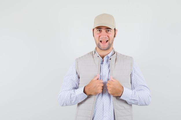 若い男はシャツ、ノースリーブのジャケット、キャップで彼の襟を調整し、自信を持って、正面図を探しています。