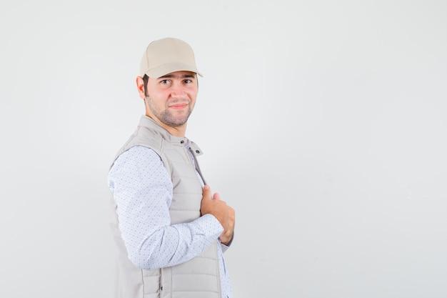若い男はシャツ、ノースリーブのジャケット、キャップで彼の襟を調整し、自信を持って見えます。 。