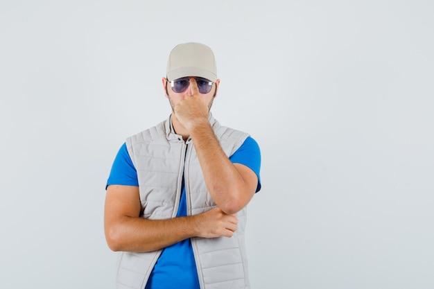 Tシャツ、ジャケット、キャップで眼鏡を調整し、自信を持って見える若い男。正面図。