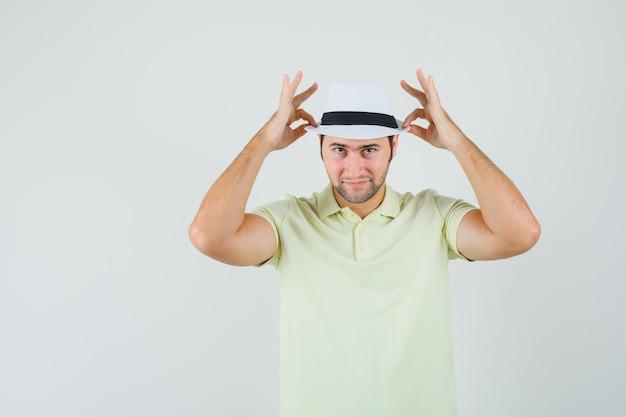 若い男はtシャツで帽子を調整し、自信を持って見える