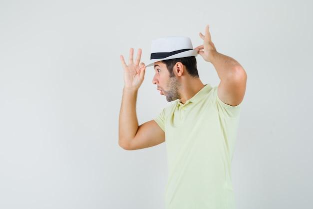 若い男がtシャツで帽子を調整し、驚いて見える
