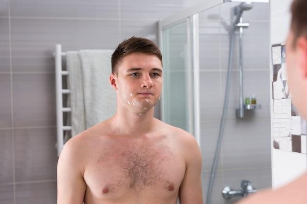 집에 있는 현대적인 타일 욕실에서 거울 앞에 서 있는 나쁜 면도 후 젊은 남자