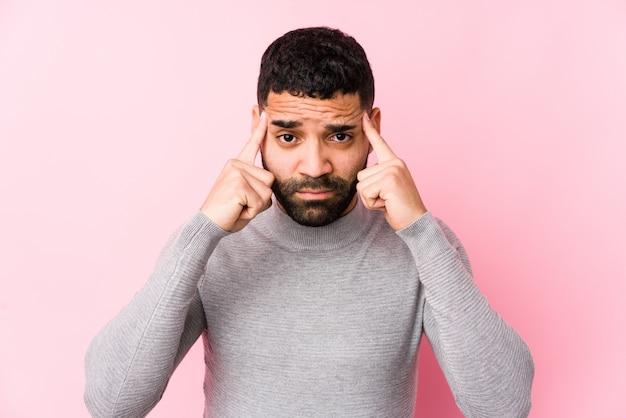 孤立したピンクの壁に若い男が人差し指を指して頭を維持するタスクに焦点を当てた