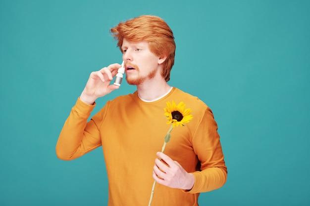 Молодой человек с аллергией на запах подсолнухов распыляет противоаллергическое лекарство в маленькой пластиковой бутылке в нос у синей стены