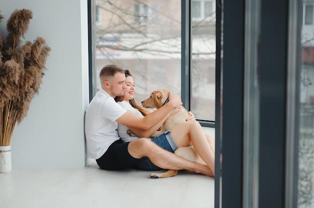 Молодой мужчина и женщина играют дома с собакой