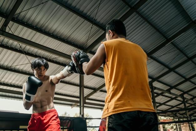 훈련 캠프에서 복싱 링에 펀치 패드와 함께 젊은 남자와 코치 훈련