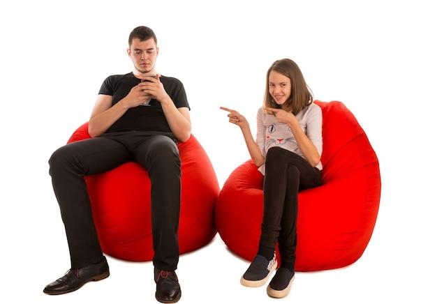 白で隔離の赤いお手玉の椅子に座っている若い男と面白い女の子