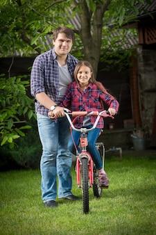 公園でリラックスして自転車に乗る若い男と女