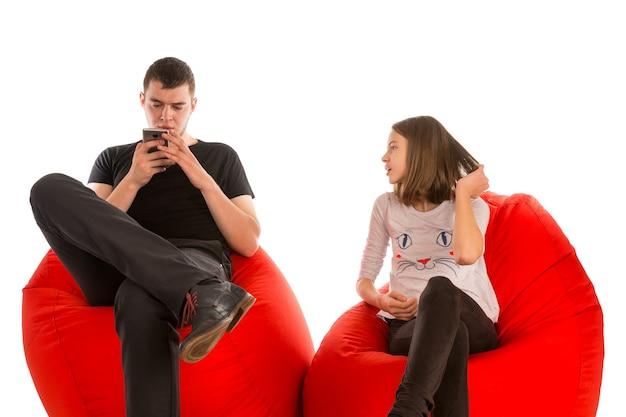白で隔離の赤いお手玉の椅子に座っている若い男と少女