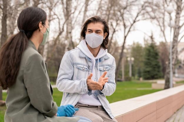 보호 마스크와 캐주얼웨어에 젊은 남자와 그의 여자 친구가 뭔가 논의