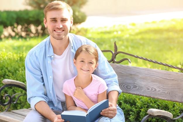 Молодой человек и его маленькая дочь читают книгу в парке