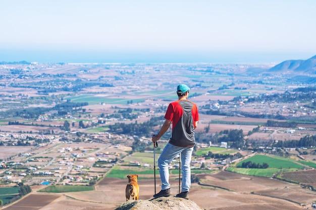 地平線を見つめている街の上の山に立っている若い男と彼のペット