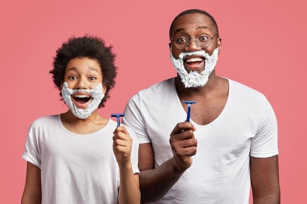 젊은 남자와 그의 아들이 얼굴에 거품을 면도하고 면도기를 들고 무료 사진