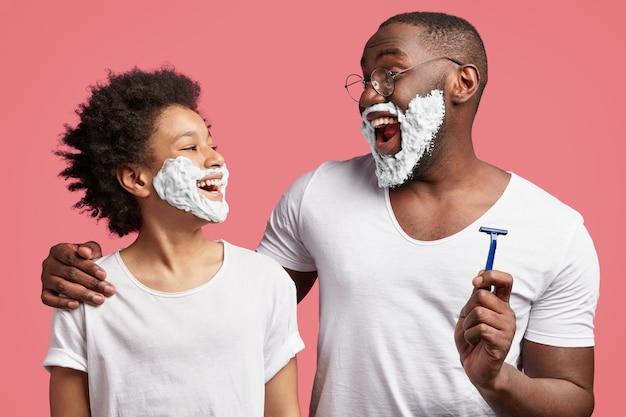 젊은 남자와 그의 아들이 얼굴에 거품을 면도하고 면도기를 들고
