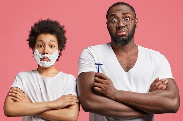 Молодой человек и его сын с вьющимися волосами, держа бритву