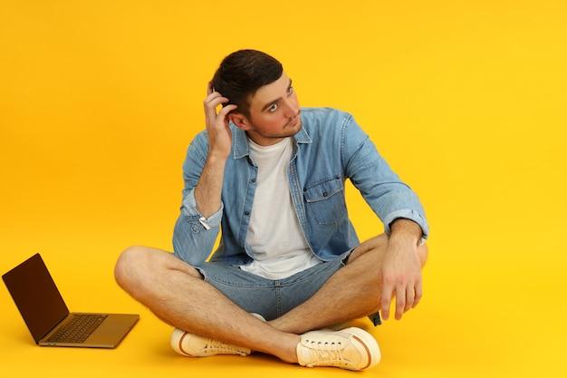 Молодой человек и ноутбук на желтом фоне.
